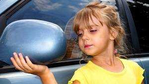Girl Looking her at the Car Mirror